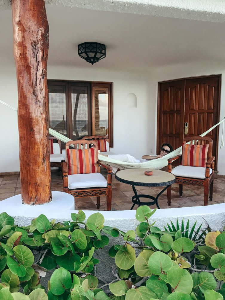 Our large private thatched-roof terrace, decked out in hand-carved furniture and a colourful hammock