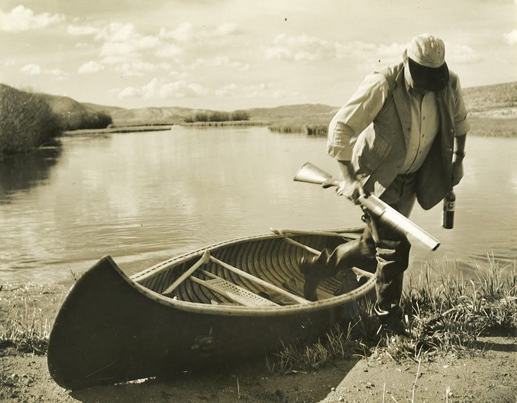 Ernest Hemingway stepping out of a canoe