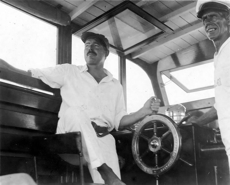 Ernest Hemingway at the wheel of his boat, Pilar, with Carlos Gutierrez