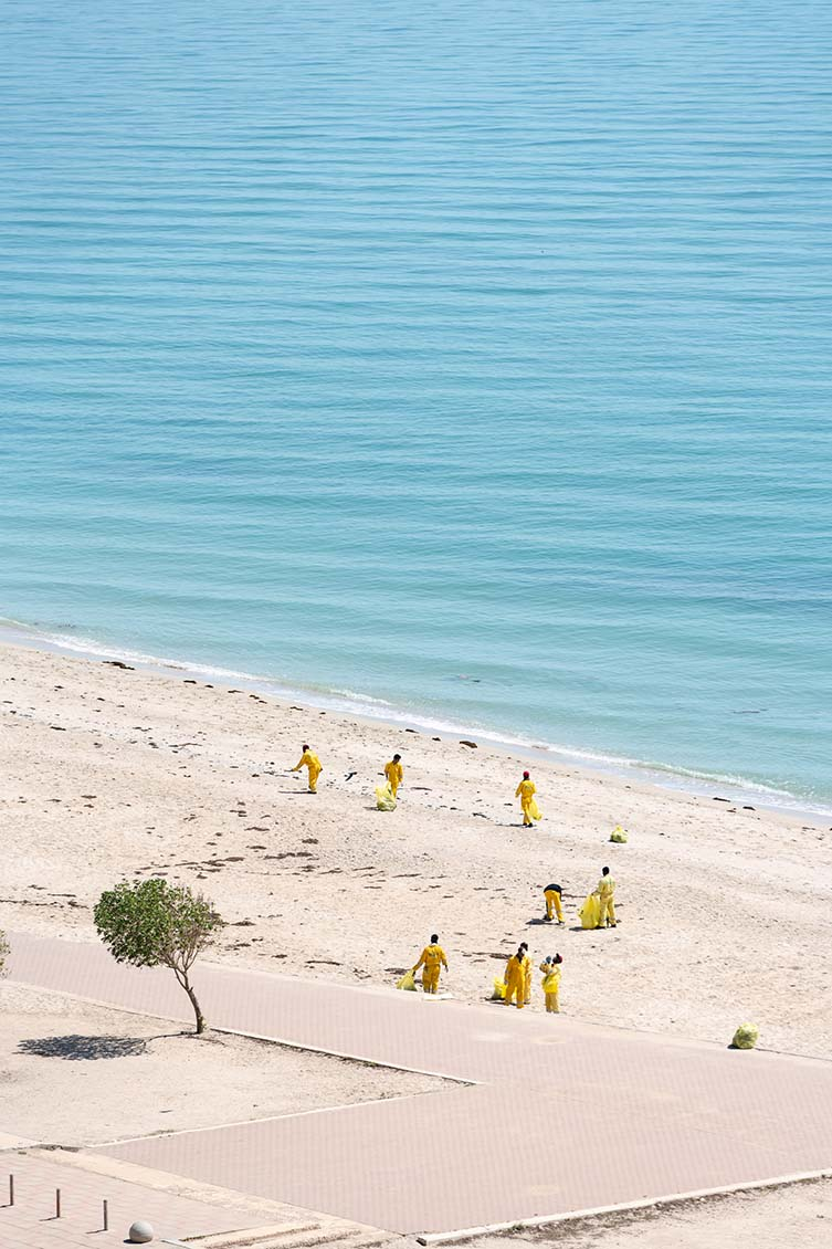 Aidan Brooks is shooting the largely empty beach from his window in Salmiya, Kuwait; this images sees workers dressed in yellow overalls cleaning seaweed after a few days of bas weather