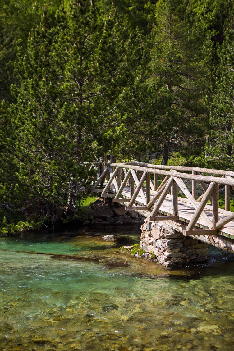 A bridge spans on of the crystal clear alpine rivers in the Parc Nacional d'Aigüestortes i Estany de Sant Maurici